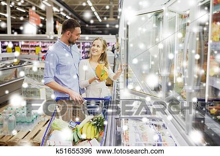 Couple With Shopping Cart Buying Food At Grocery Stock Photograph