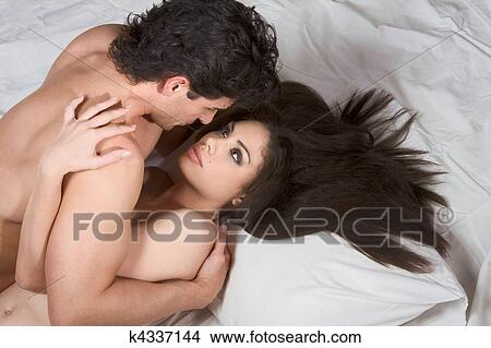 Loving Affectionate Nude Heterosexual Couple On Bed Making Love
