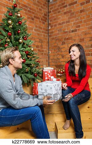 happy sweet young couple prepared christmas gifts for decoration