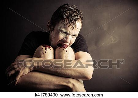Psychotic And Angry Teen Chews His Knees Stock Photography K41789490