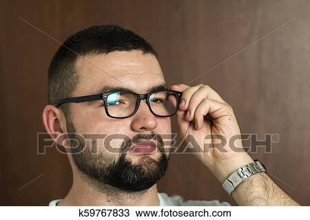 1e6c6dfeda66 Portrait of handsome bearded black haired intelligent modern young man in  glasses with short haircut and kind black eyes smiling on blurred  background.