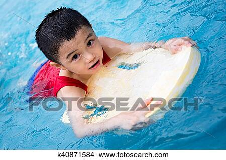 35dec6738d Asian Chinese Little Boy Swimming With Floating Board at Outdoor Swimming  Pool.
