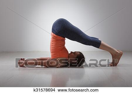sporty woman practices yoga asana halasana picture