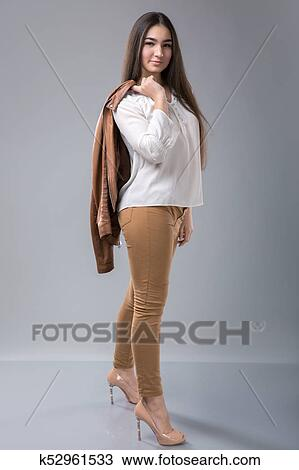 576926e3335 ... beautiful young business woman standing with hand holding jacket behind  her shoulder against grey background and posing fashionable. Looking at  camera.