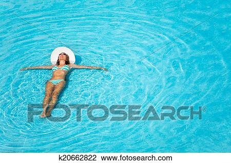 Girl With Hat Swimming In Crystal Clear Pool Stock Image