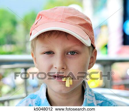 29be655318755 Cute little boy eating french fries in cafe