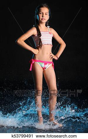 Adorable Young Teenage Girl In A Swimsuit Stands Barefoot In Splashing Water Pretty Child With Dark Hair Beautiful Face And A Slim Figure