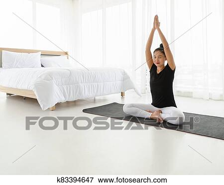 middle aged women practicing yoga in easy seat pose or