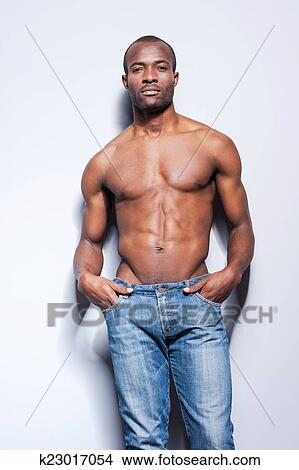 d930d04a0 Confident handsome. Handsome young shirtless African man looking at camera  and holding hands in pockets while leaning at the grey wall