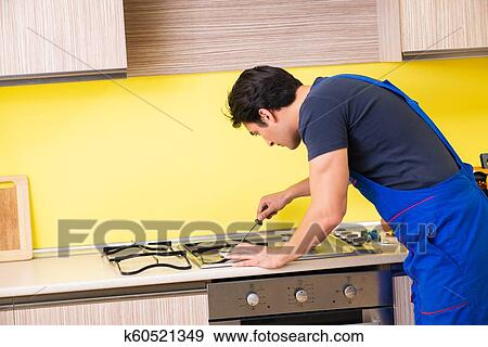 Young service contractor assembling kitchen furniture Stock