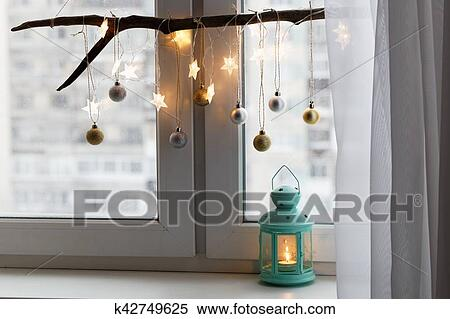 christmas decoration and lantern with candle on a window sill
