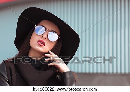 7e78bdf59f34 Street portrait of beautiful woman in trendy black coat and stylish hat.Female  fashion concept