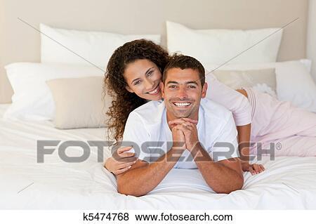 images joli femme treindre elle mari sur leur lit chez soi k5474768 recherchez des. Black Bedroom Furniture Sets. Home Design Ideas