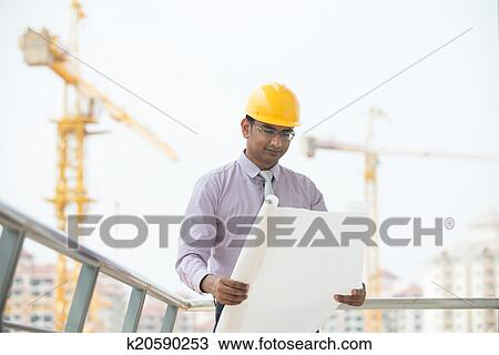 d9ad1a015a0 Stock Photo of indian male engineer reading plans with construction ...