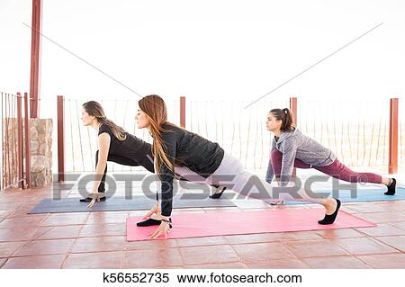 group of women in low lunge yoga pose stock photography