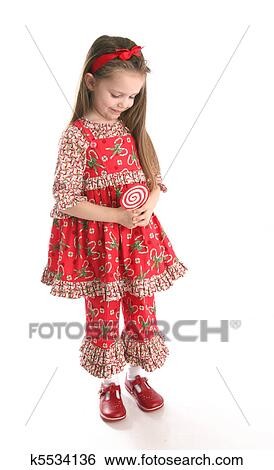 1141f5ea22a1 Adorable preschool girl wearing a Christmas holiday outfit posing holding a  lollipop, isolated on white