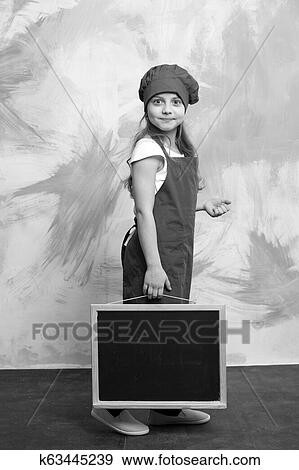 72a4391ba4d Small baby girl or cute child with happy face in red chef hat and cook apron  holding blackboard on colorful abstract background