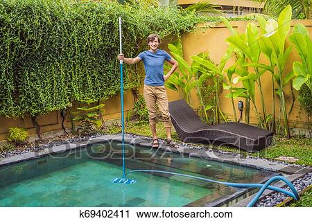 Cleaner of the swimming pool. Man in a blue shirt with cleaning equipment  for swimming pools. Pool cleaning services Stock Image