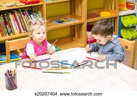 Deux Peu Gosses Dessin à Coloré Crayons Dans Préscolaire à Les Table Petite Fille Et Garçon Dessin Dans Jardin Enfants Image