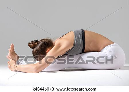young woman in paschimottanasana pose grey studio