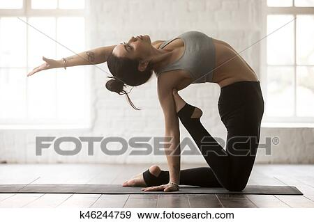 young attractive woman in camel pose white loft studio