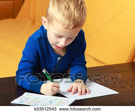 Blond boy child kid with pen writing on piece of paper. At ...
