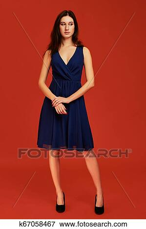 d3240dd90f17 Picture - Beautiful young brunette woman in elegant blue cocktail dress and  black high heels is