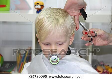 Blond Kleiner Junge Schneiden Ihr Haar In A Childrens Friseur Stock Fotografie
