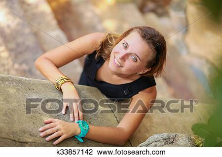 d139774b4a4 Outdoor summer portrait of young beautiful girl with blond hair posing in short  black stylish dress standing on the stairs.