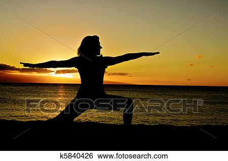 A Woman Assumes The Warrior Pose In Yoga On Beach At Sunset