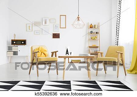 Bright Living Room Interior With Retro Armchairs Next To A Wooden Table And Carpet Geometric Pattern