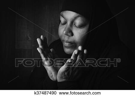 stock photography of muslim woman praying in black and white
