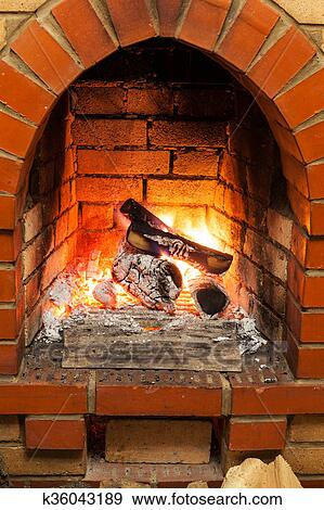 Ash Coal And Burning Billets In Fireplace Stock Photo
