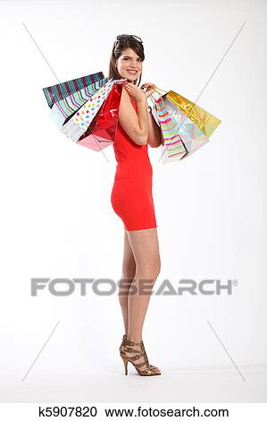 Beautiful Hy Young Caucasian Woman Holding Ping Gift Bags Over Her Shoulders Model Is Wearing Gold Heels And A Short Red Dress