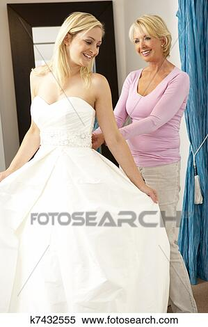 Bride Trying On Wedding Dress With Sales Assistant Stock