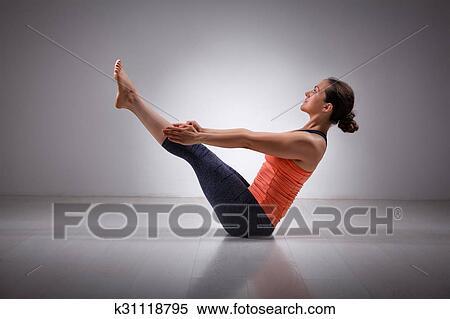 woman practices yoga asana paripurna navasana stock