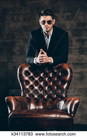 0511d537db82 Young handsome man in suit and sunglasses leaning on leather chair and  looking at camera while standing against dark grey background