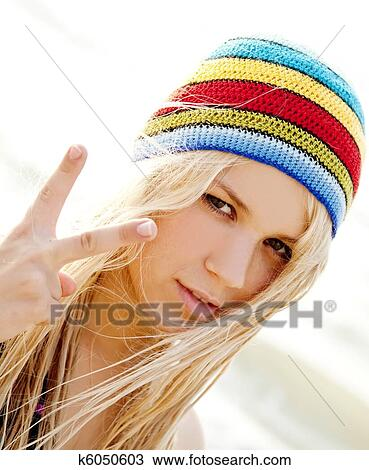 Beautiful young blonde girl in rastafarian hat at sunrise. Photo with  counter-light on background. 97a6ce831c86
