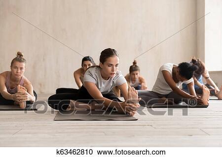 grupo pessoas prática ioga cabeça para joelho