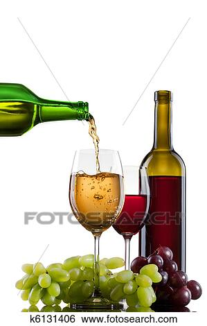 stock images of white wine pouring into glass with grape and bottles