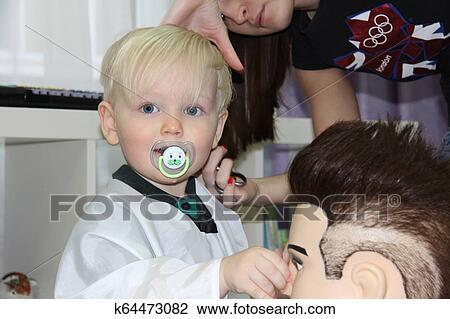 Blond Kleiner Junge Schneiden Ihr Haar In A Childrens Friseur Stock Bild