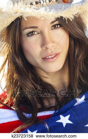 097474da60de7 Beautiful young brunette girl or young woman smiling wearing straw cowboy  hat and wrapped in American flag towel on a sunny beach