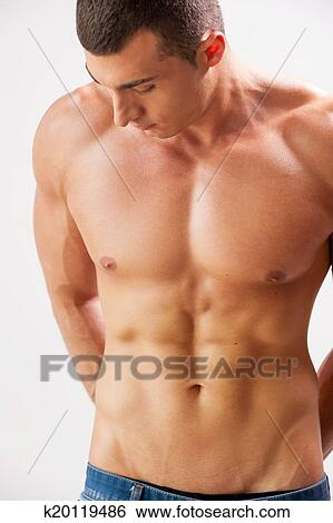 5aa4c6714 Stock Photograph - Confident in his body. Handsome young muscular man  holding hands behind back