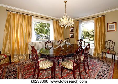 eetkamer met gele gordijnen en groene muren