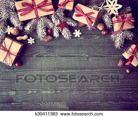Seasonal Rustic Christmas Border Composed Of Decorative Gifts Pine Branches Nuts And Snowflake Ornaments Over A Wooden Background With Copyspace