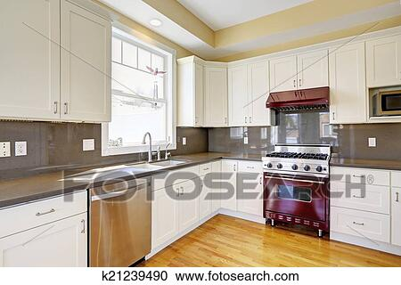 White Kitchen With Burgundy Stove And Grey Counter Tops Stock Image
