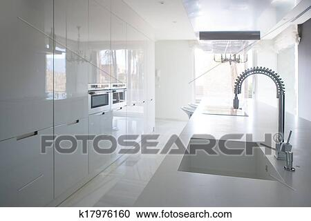 Modern white kitchen perspective with integrated bench Stock Image