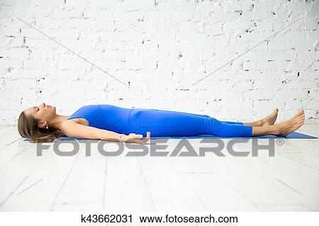 young attractive woman in dead body pose white studio