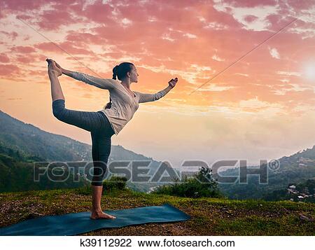 frau machen joga asana natarajasana draußen an