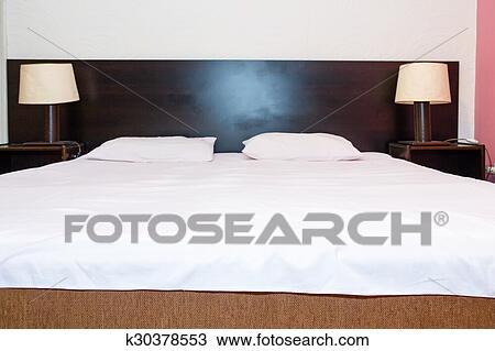 Archivio fotografico letto con bianco fogli e cuscini con